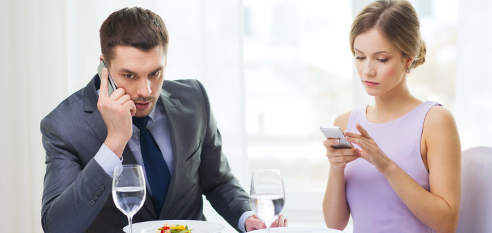 restaurant, couple, technology and holiday concept - busy couple